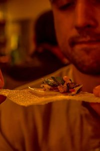Man eats chip loaded with silkworm salad